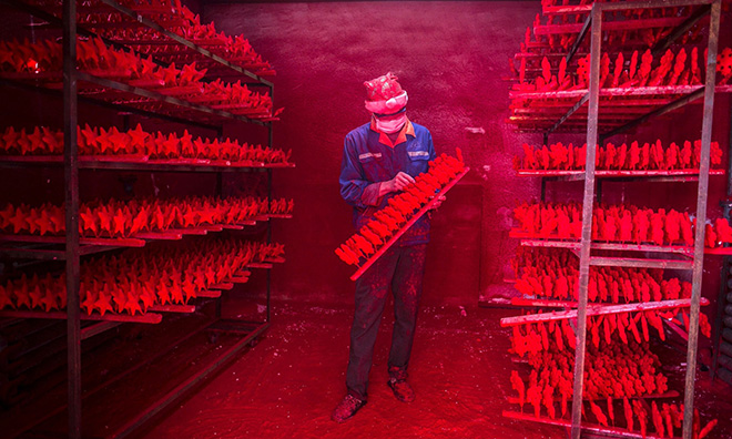 The two men produce 5,000 red snowflakes a day, and get paid around £300 a month. Photograph: China Daily/Reuters