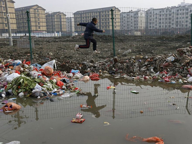 A child is reflected in a drainage ditch as he jumps over trash at a village which will soon be demolished, on the outskirts of Jiaxing city, Zhejiang province, January 12, 2013