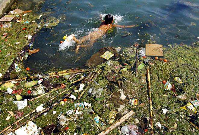 A child swims in a polluted reservoir in Pingba, southwest China's Guizhou province, Sept. 2, 2006