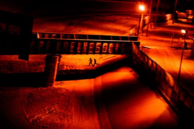 ©Paolo Pellegrin - Due uomini che cercavano di entrare illegalmente negli USA corrono lungo il letto asciutto del fiume Rio Grande nei pressi di Ciudad Juárez, in Messico, dopo essere stati scoperti dalla polizia di confine statunitense. El Paso, Texas. U.S.A. 2011