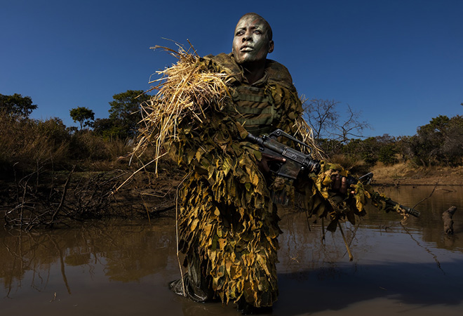 World Press Photo 2019, Environment, Singles, Winner - Akashinga - the Brave Ones © Brent Stirton, Getty Images. Akashinga (The Brave Ones) is a ranger force established as an alternative conservation model. It aims to work with, rather than against local populations, for the long-term benefits of their communities and the environment. Akashinga comprises women from disadvantaged backgrounds, empowering them, offering jobs, and helping local people to benefit directly from the preservation of wildlife. Petronella Chigumbura (30), a member of the all-female anti-poaching unit, participates in stealth and concealment training in the Phundundu Wildlife Park, Zimbabwe.