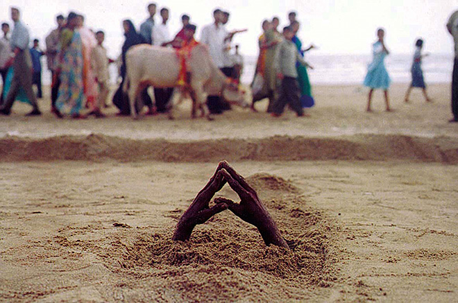Ashish Gupta - A man buries himself under the sand, 2002. Juhu beach Mumbai, cm 45x69
