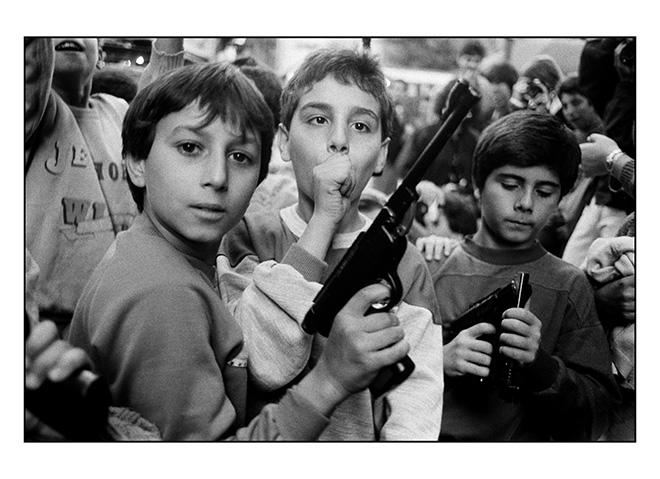 Letizia Battaglia - Palermo, 1986. Festa del giorno dei morti. I bambini giocano con le armi